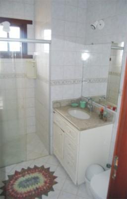 Banheiro social com gabinete, ducha higiênica e box em blindex